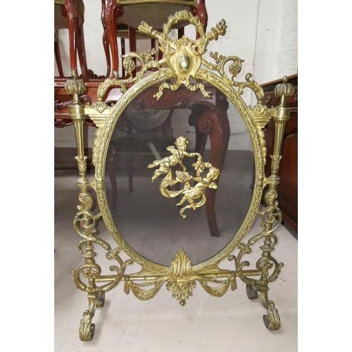 536 - An ornate gilt metal firescreen with acanthus scrolls and cherub mounts...