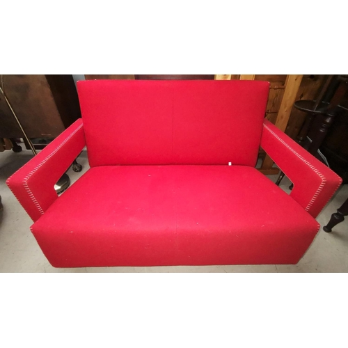 557 - A Cassina two seater settee in red fabric with stitchwork to the arms, designed by Gerrit Thomas Rie...
