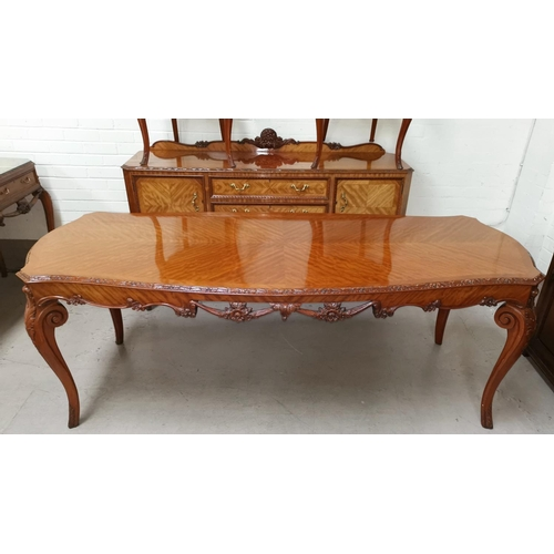 537 - A Louis XV style carved and quarter veneered dining suite in the manner of Epstein, comprising shape...