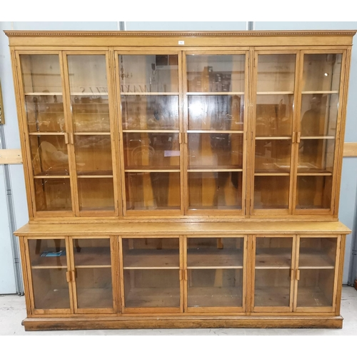 556 - An early 20th century oak large library bookcase enclosed by 5 upper and 5 lower glazed doors...