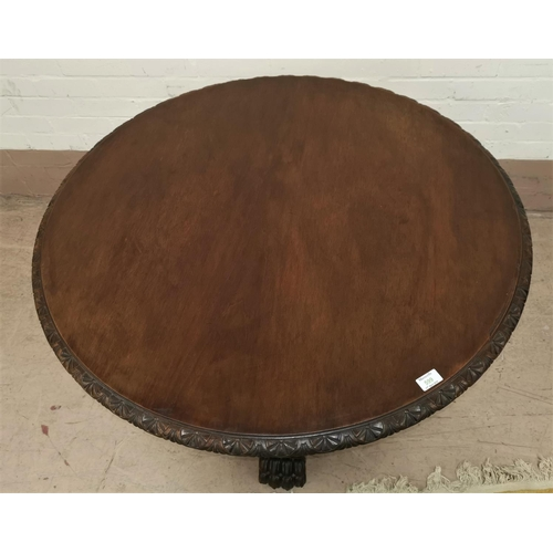 599 - A 19th century mahogany continental circular library table on heavily carved base, scroll supports a...
