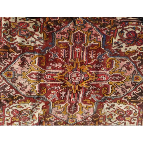 628 - A large hand knotted rust ground carpet with geometric pattern, 137