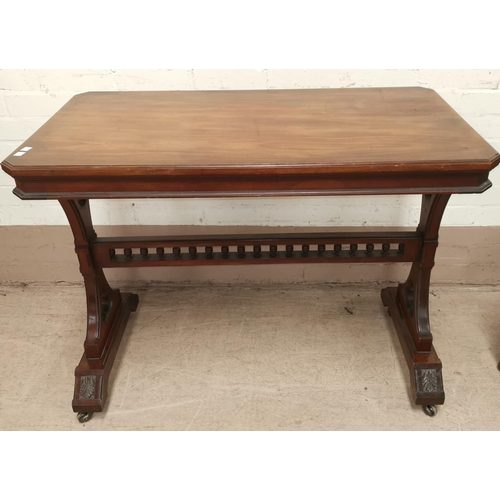 646 - A late 19th / early 20th century walnut Gothic style library table with carved and pierced supports ...