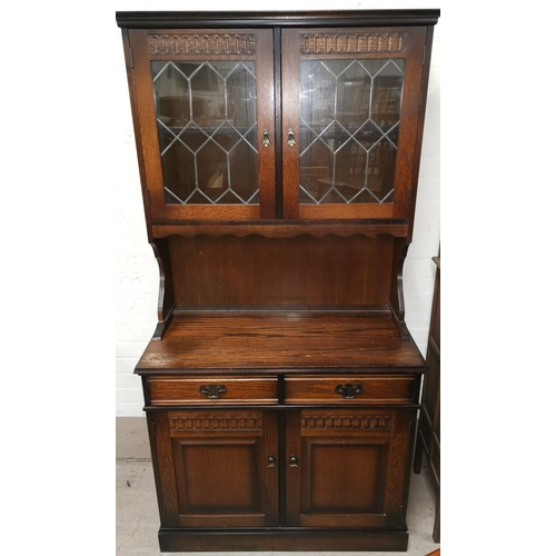 641 - A Jacobean style oak dresser with leaded glass doors above, over 2 cupboards and 2 drawers...