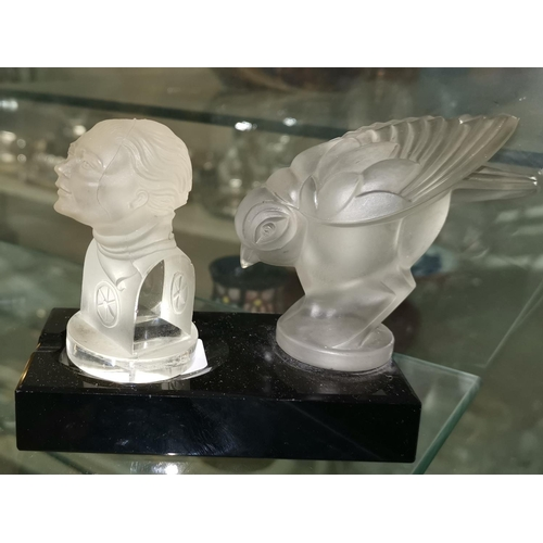 176 - An Art Deco black glass ashtray with frosted bird mount; a similar miniature bust...