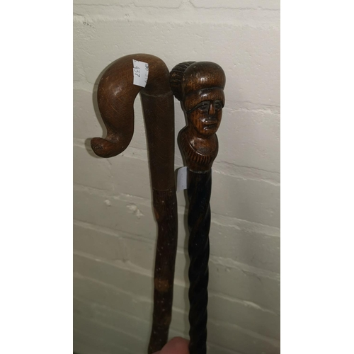 437 - A novelty walking stick with facemask terminal; a crook; a gilt mirror...