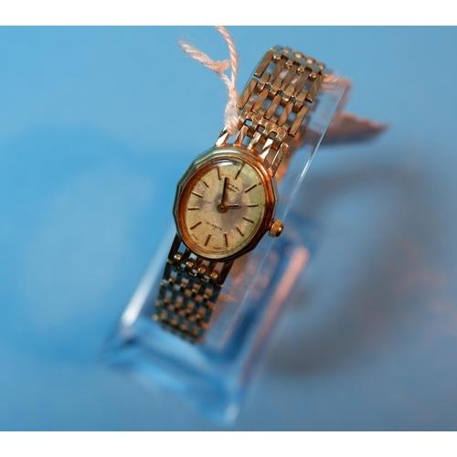 395 - A ladies 9 carat hallmarked gold wristwatch on integral gate bracelet strap, 18 gm gross...