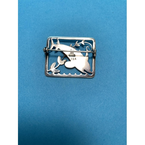294 - A Danish sterling silver brooch designed by Arno Malinowski for Georg Jensen, with two leaping dolph...