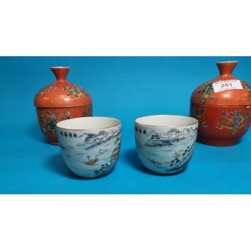281 - A pairof Chinese covered jars with reversable cup / covers decorated in polychrome against an orange...
