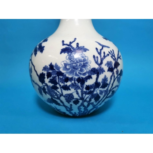 283 - A spherical Chinese vase with tall slender neck in underglaze blue with flowering branches, concentr...
