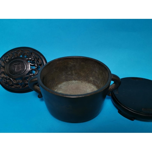 284 - An oval bronze 2 handled Chinese censor with pierced lid, relief character signature to base and har...