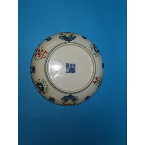 288 - A Chinese porcelain shallow dish decoarted with scrolls and leaves in underglaze blue, orange and gr...