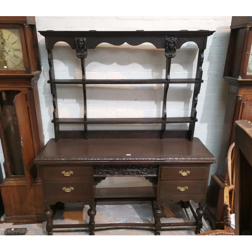 540 - An early/mid 20th century carved oak Welsh dresser with facemasks to the delft rack, 4 drawers below...