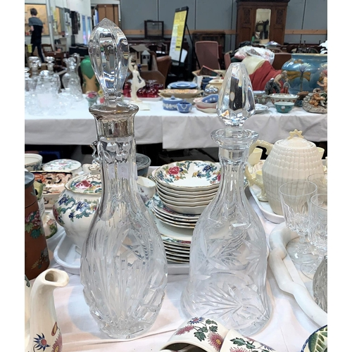 192 - A cut glass decanter with silver rim, stamped '925'; another cut glass decanter...
