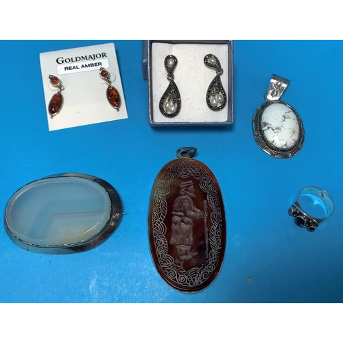 296 - An oval brown hardstone pendant with intaglio figure of a man with staff; a white metal and marbled ...