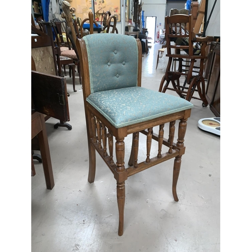 551 - An Edwardian music chair with spindle gallery, green brocade upholstered eat and back; a square foot...