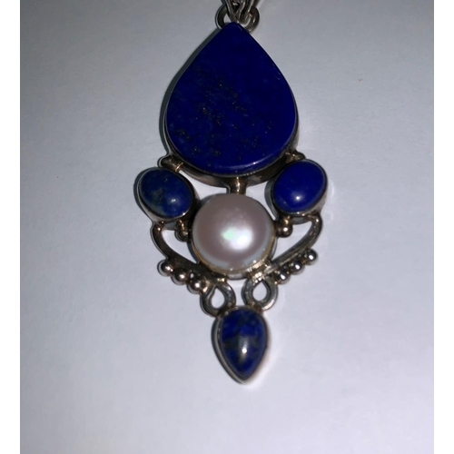 195a - An Art Nouveau style pendant on chain, stamped 925, set with lapis lazuli coloured stones and centra...