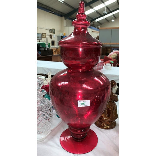 197 - A pharmacy display jar and cover in red lustre glass...