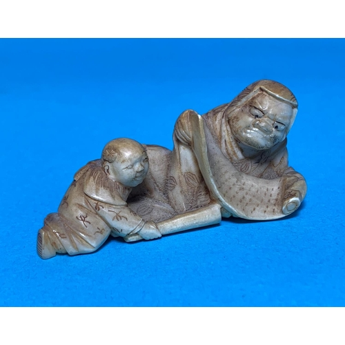 460 - A Meiji period netsuke depicting a man with scroll and child, length 6cm...