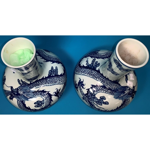 181 - A Chinese pair of globular vases with underglaze blue decoration of dragons, 12