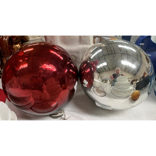 198 - A large silvered glass mirror ball; another in red glass...