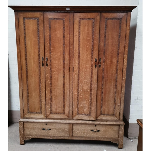 547 - An early 20th century oak Arts & Crafts wardrobe by Arthur W Simpson of Kendal, with lines of carved...