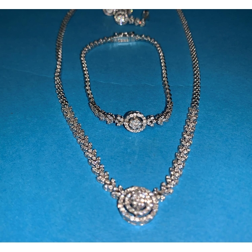 329 - A modern white gold and diamond suite of necklace, bracelet and earrings, the necklace with central ...