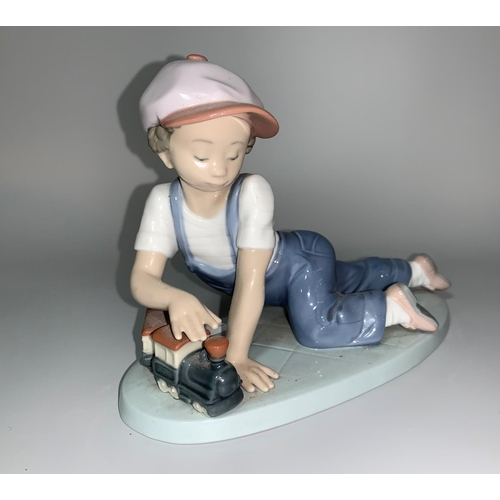 7 - A Lladro figure - boy kneeling and playing with a toy train, stamped 'Collectors' Society 1992', imp...