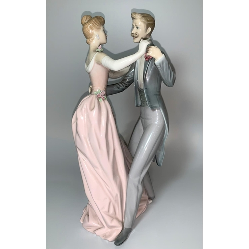 11 - A Lladro group - An Edwardian lady and gentleman in evening dress, waltzing, height 31cm...