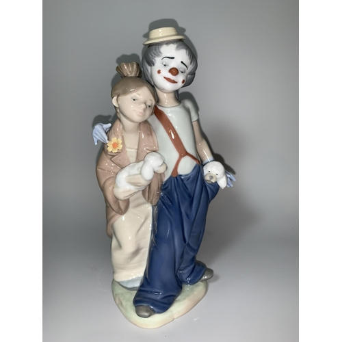 12 - A Lladro group - a young girl holding a puppy leaning against a young clown with a puppy in his pock...