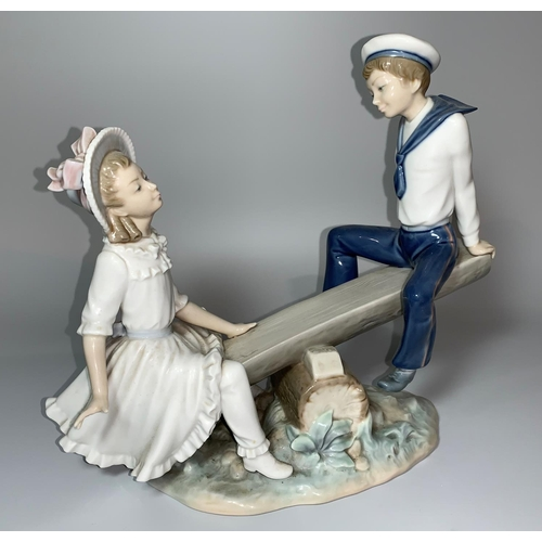 16 - A Lladro group - girl and boy in sailor outfit on a sea saw, overall length 27cm (1 finger a.f.)...