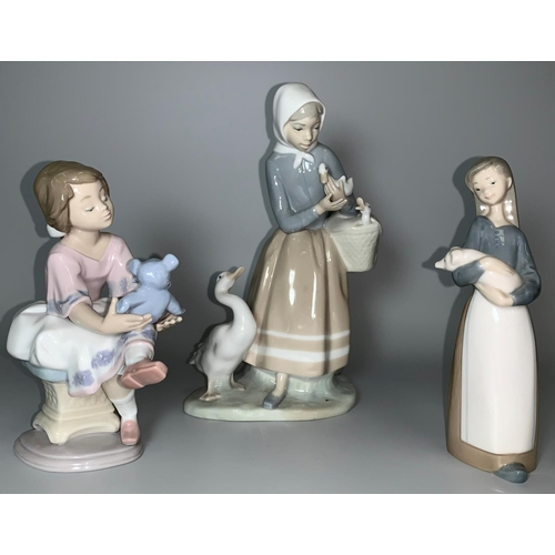 21 - Two Lladro figures - girl on a stool holding a Teddy bear and a girl holding a piglet; a Lladro grou...