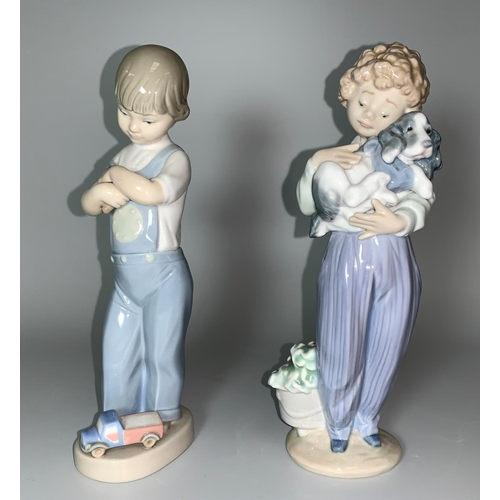 22 - 2 Lladro figures - boy holding a spaniel and boy with dice and toy truck (small firing crack to dog ...