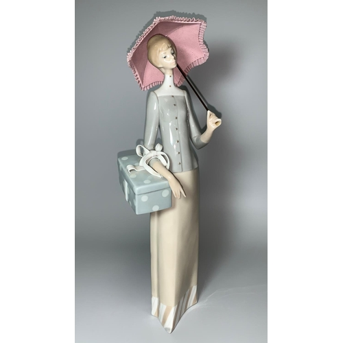26 - A Lladro figure of a lady with parasol holding a gift parcel...