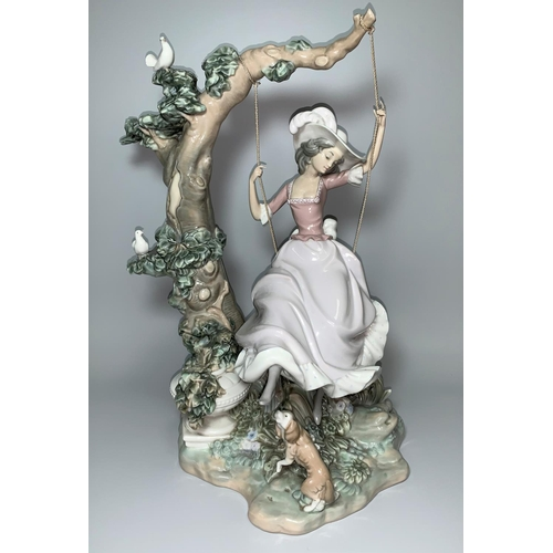 27 - A large impressive Lladro group of a girl with full skirt and feathered hat on a swing from the bran...