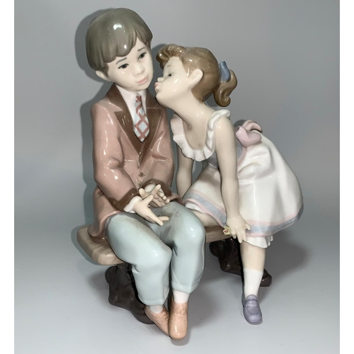 4 - A Lladro group - girl kissing a boy seated on a bench, 10th Anniversary 1985-1995...
