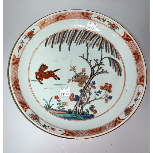 291a - A Chinese Kangxi shallow dish decorated with prancing horse, flowers and trees, in burnt orange, gre...