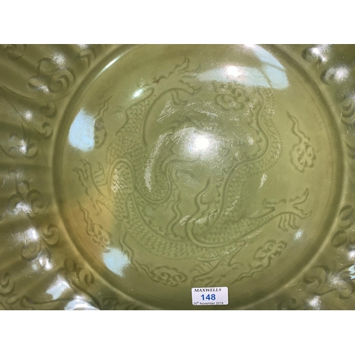 148 - A large Chinese 'Ming' style charger with wavy border decorated in relief with central dragon under ...