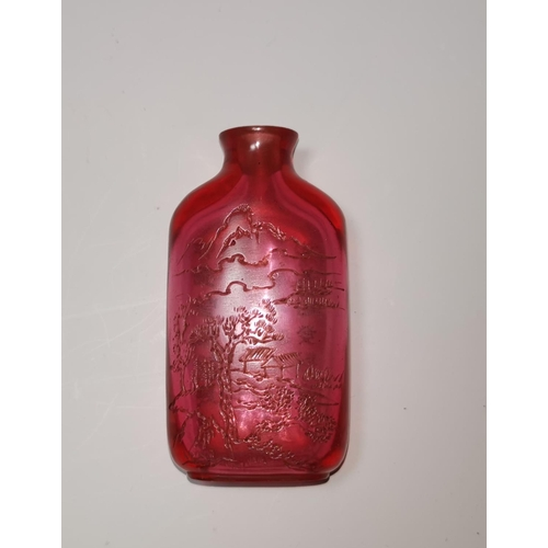 143 - A Chinese ruby coloured glass snuff bottle engraved with landscapes to one side, 28 character text t...