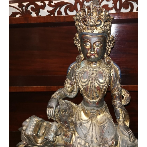243 - A large Chinese gilt-bronze figure of Guanyin seated on a ferocious Buddhist lion, on lotus base, he...