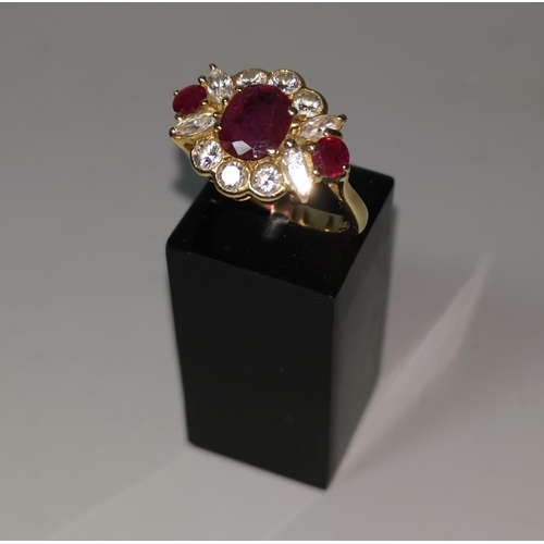 369 - An 18 carat hallmarked gold ruby and diamond dress ring, set oval central ruby and 2 rubies either s...