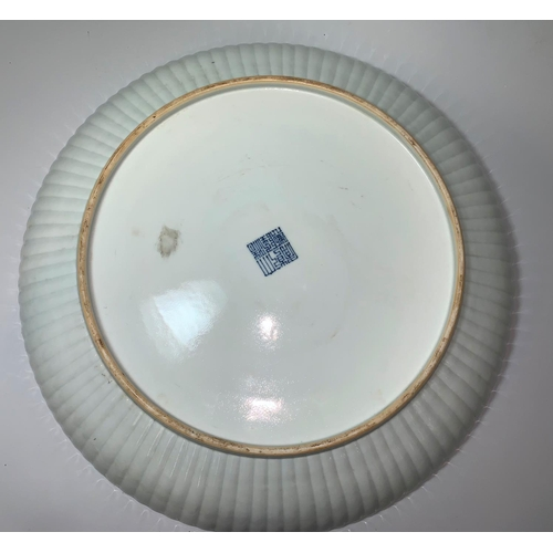147 - A large Chinese 'Qing' white glazed shallow dish with raised fluted border, underglaze blue seal mar...