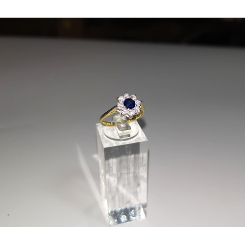 120 - A ladies dress ring set sapphire surrounded by 8 diamonds, 18 carat gold shank...