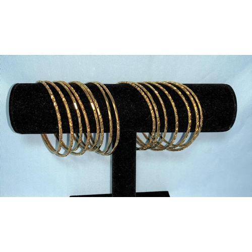 284 - Fifteen Egyptian yellow metal marriage bangles with relief decoration, bearing Egyptian hallmarks, t...