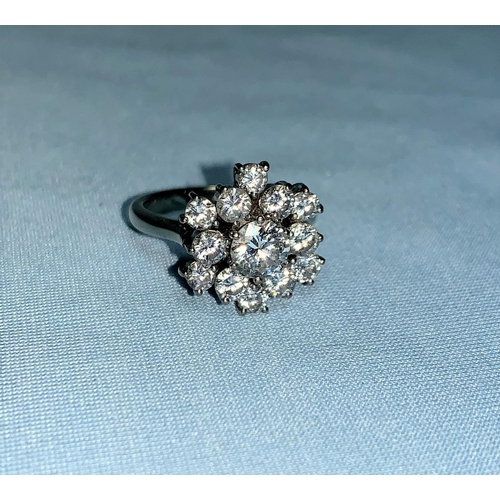 350 - A large white metal diamond cluster ring, set central stone of approx. 0.7 carat, surrounded by 12 s...