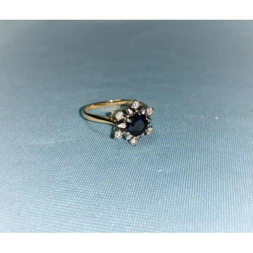 409 - A dress ring set sapphire and diamonds, the shank marked '18 ct'...