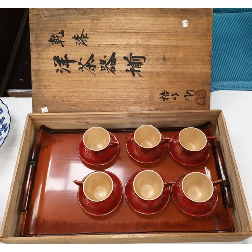100b - An oriental set of 6 red lacquer cups and saucers, with inscribed rectangular box, 56 x 34 cm...