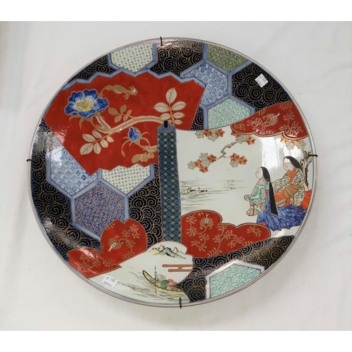 101a - A large Japanese Imari porcelain saucer dish, decorated with 2 figures on a scroll laid over a panel...