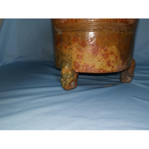 105 - A Chinese Tang dynasty terracotta urn of tapering cylindrical form, carried on 3 figural feet, glaze...