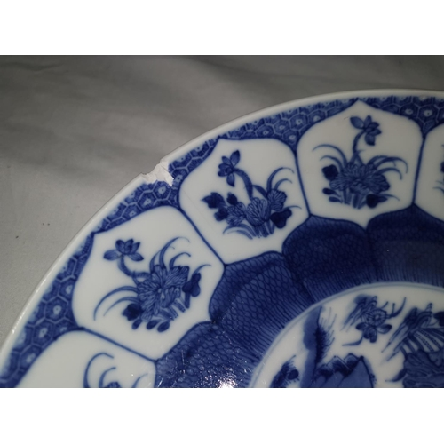 112 - An 18th century Chinese blue and white dish with floral border and traditional scene to the centre, ...